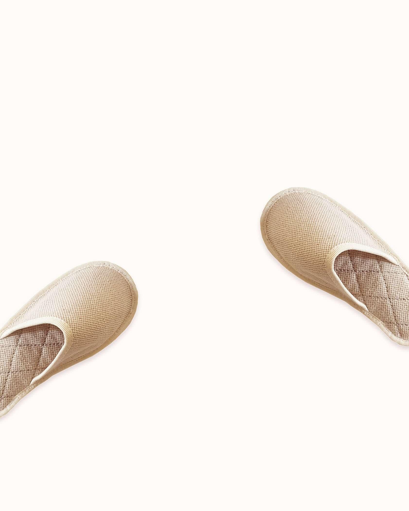 Chausson français pour enfant fabriqué en France. Modèle Petite Flamme (beige et blanc), une pantoufle comme à l'hôtel vêtue d'un rembourrage matelassé et d'une finition sophistiquée.