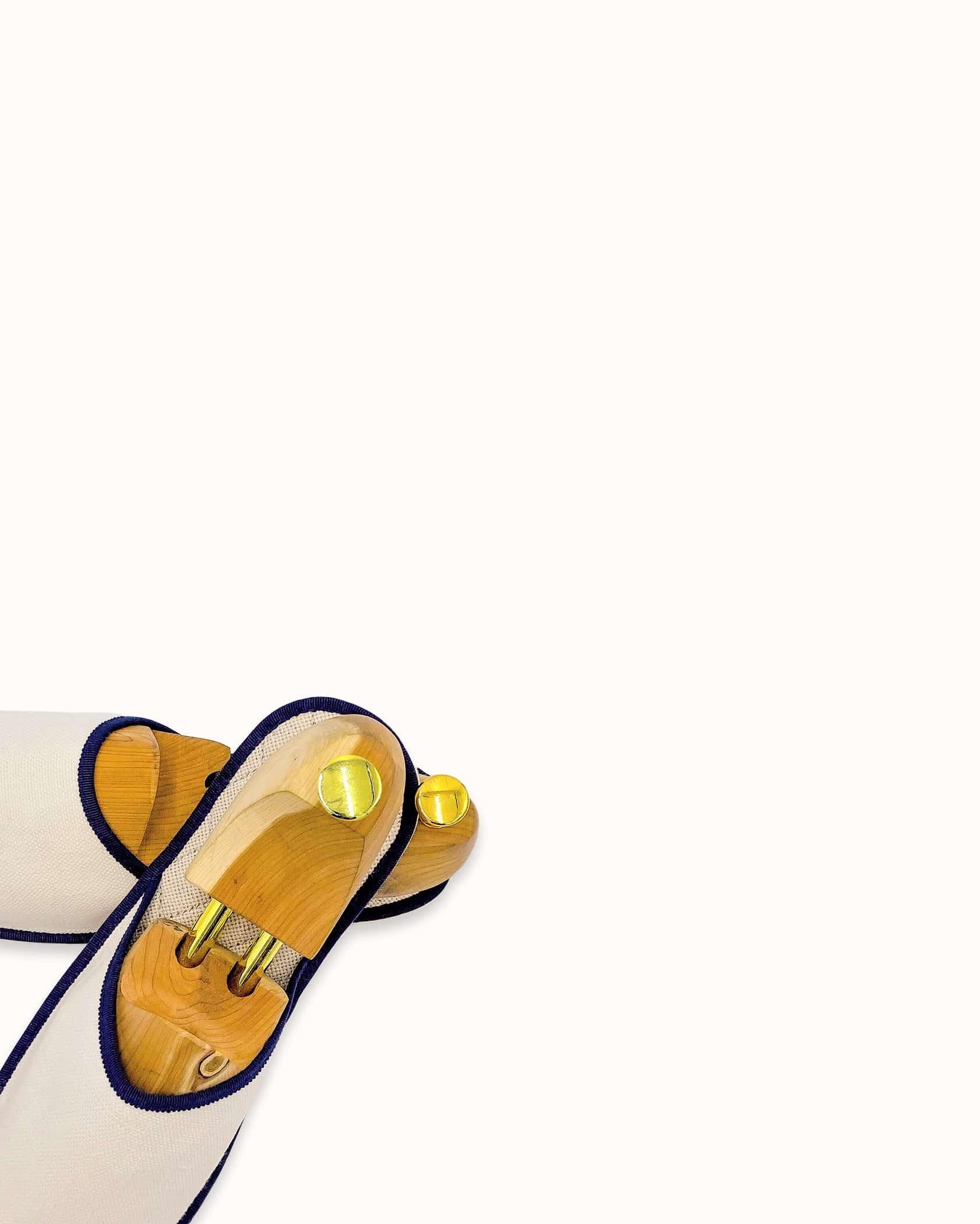 Chausson français pour homme, femme et enfant fabriqué en France. Modèle Albâtre (blanc et marine), une pantoufle comme à l'hôtel vêtue d'un rembourrage matelassé et d'une finition sophistiquée.
